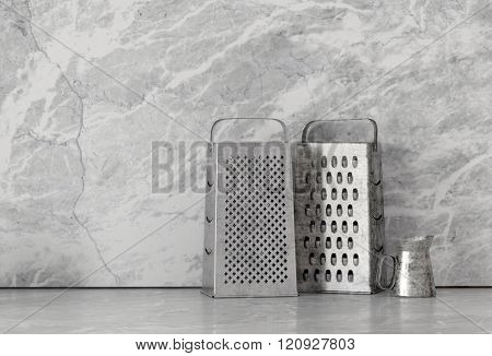 Cheese graters and container in stainless steel finish over smooth marble granite surface. 3d Rendering.