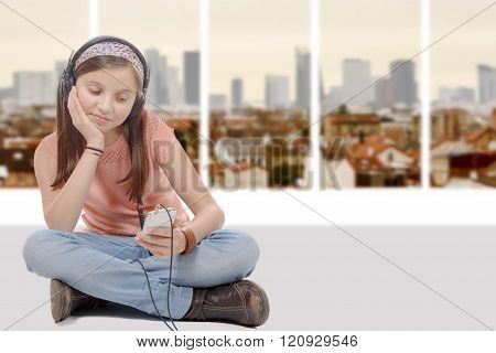 preteen girl listening to music with his smartphone, sitting cross-legged