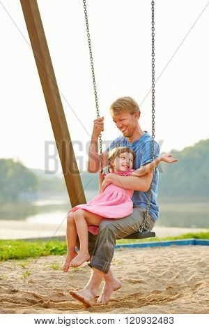 Father and daughter swinging together on a swing on a playground in summer