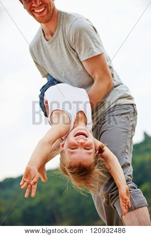 Father letting his laughing daughter fly on his arms in summer