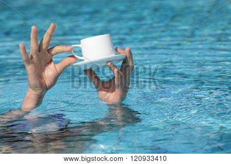 hands above water holding cup of coffee  - close up