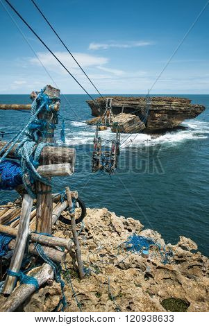Cable car lift between Timang beach coast and small rocky island in the ocean. Java, Yogyakarta, Indonesia