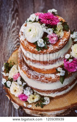 Homemade wedding naked cake  decorated with flowers on wooden cut stand, shot from top