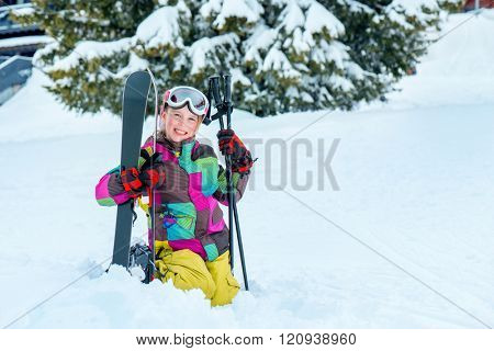 Happy kid sitting in snow with skis