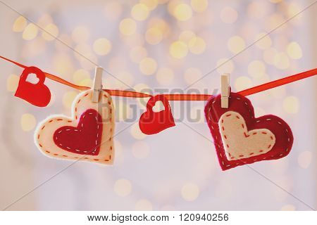 Hanging Valentines Hearts on blurred lights background
