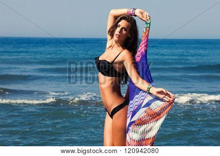 tanned young woman in bikini and colorful sarong on sea beach sunny summer day