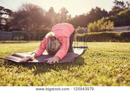 Senior woman doing yoga outdoors in gentle morning sunlight