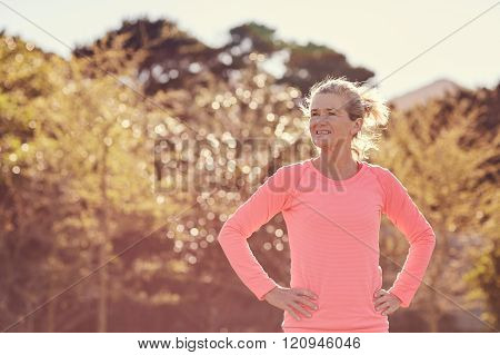 Athletic senior woman looking confident outdoors on a sunlit mor