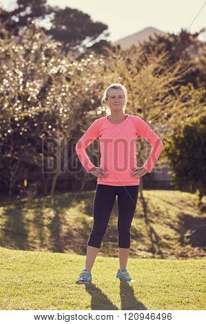 Fit senior woman outdoors looking confident with hands on hips