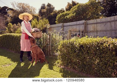Senior woman ready for gardening in backyard with her dog