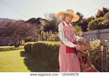 Senior woman farmer greeting her dog in the backyard