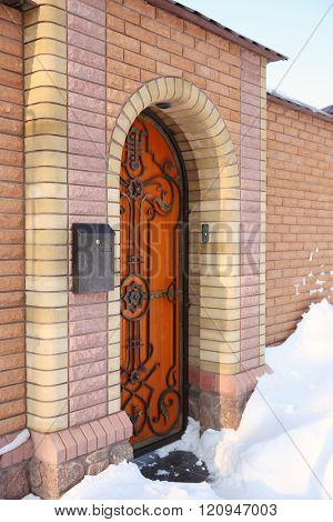 Wooden door in brick wall, wintertime