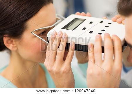health care, medicine, people, eyesight and technology concept - close up of optometrist with pupillometer checking patient intraocular pressure at eye clinic or optics store