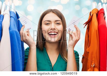 clothing, fashion, sale, shopping and people concept - happy woman showing price tags on clothes at wardrobe over blue holidays lights background