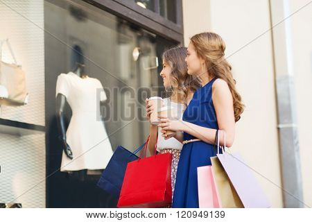sale, consumerism and people concept - happy young women with shopping bags and coffee paper cups looking at shop window outdoors