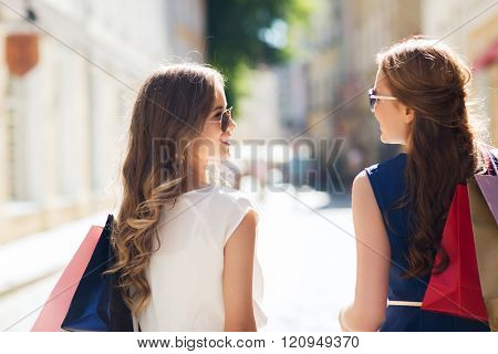 sale, consumerism and people concept - happy young women with shopping bags walking along city street and talking