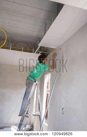 Worker Installing Gypsum Board Ceiling Of Building House Construction