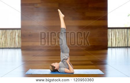 fitness, sport, people and healthy lifestyle concept - woman making yoga in shoulderstand pose on mat over wooden gym background