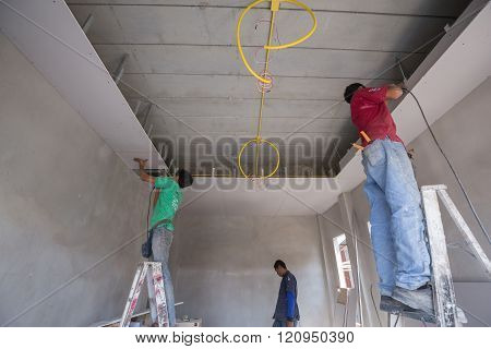worker installing gypsum board ceiling of building house