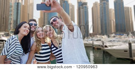 summer, sea, tourism, technology and people concept - group of smiling friends with smartphone taking selfie over dubai city harbor or waterfront background