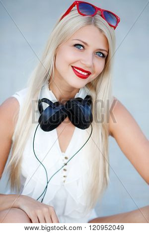 Smiling blond girl in headphones on blue background