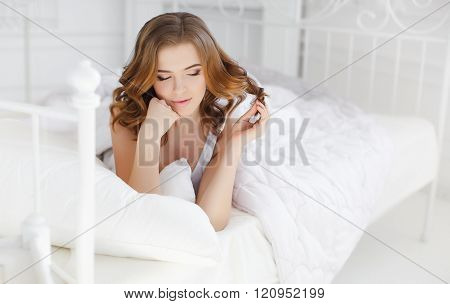 Beautiful girl wakes up in a white bed in the morning