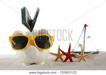 Piggy bank with inserted dollar banknotes and sunglasses on a sand, isolated on white. Holiday money concept
