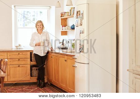 Smiling senior woman in her bright and tidy kitchen
