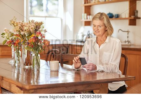Senior woman reading a message on her phone in kitchen