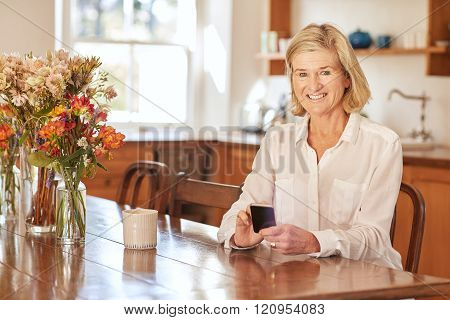 Senior woman using a smart phone at wooden table