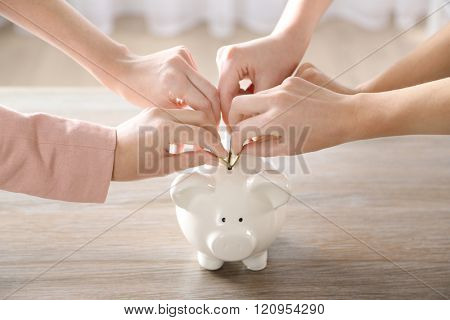 Hands putting coin into piggy bank at the table