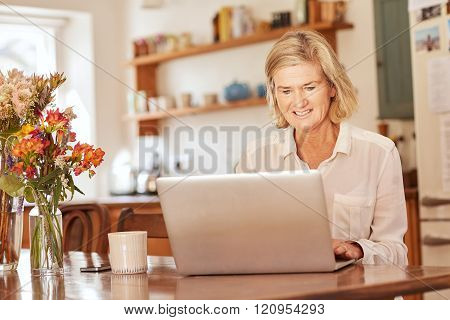 Senior woman working on a laptop in her kitchen