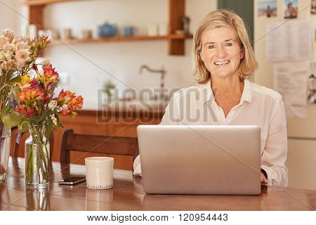Smiling senior woman with a laptop at wooden table