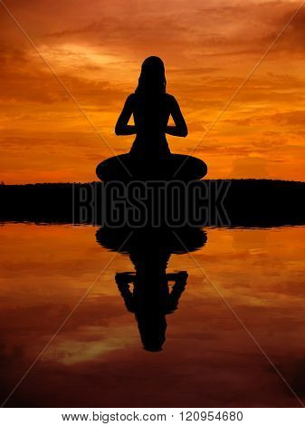 Silhouette of a beautiful Yoga woman with water reflection at sunset
