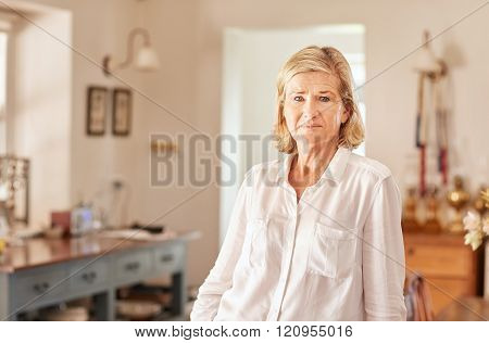 Senior woman at home with a serious facial expression