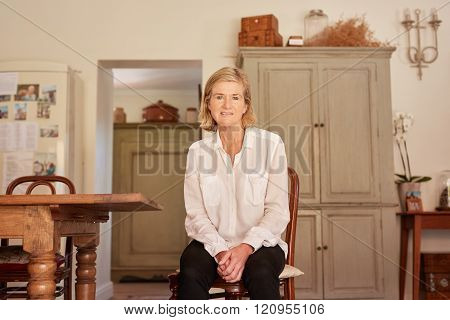 Modern senior woman sitting in her rustic style home