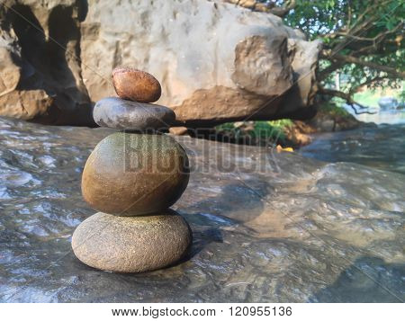 Superimposed waterfall pebble rock arranged on big stone at waterfall background with copy space