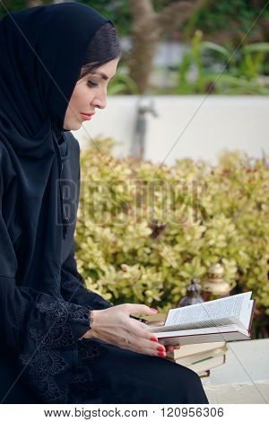 Emarati Arab woman outside reading a book, Dubai, United Arab Emirates.