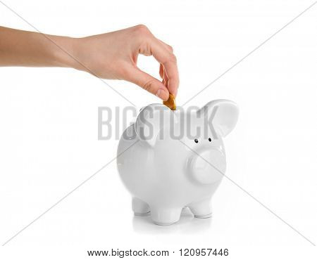 Hand putting coin into piggy bank, isolated on white