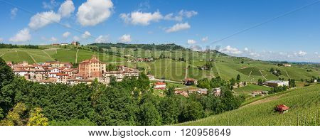 Small medieval town of Barolo and green hills and vineyard under blue sky in Piedmont, Northern Italy (panorama).