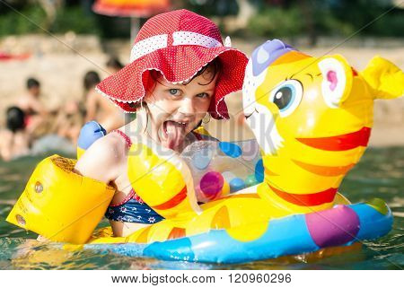 Girl Swims In The Sea On Lifebuoy And Showing Tongue