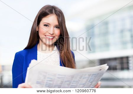 Portrait of a young business woman reading a newspaper