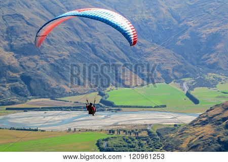 Paragliding sportsman flying high over mountains with a parachute wind break, gliding over fields with the wind