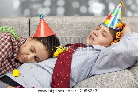 Sleeping couple in party hats at home