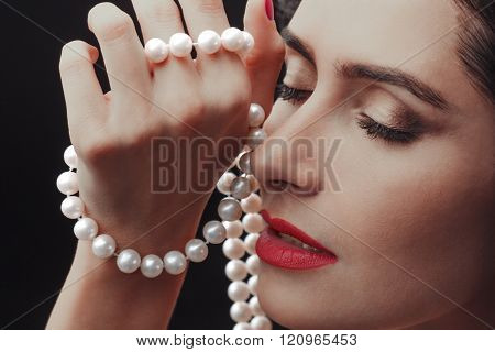 Close-up portrait of sensuality beautiful woman face with a string of pearls fashion make-up sexy evening red lips