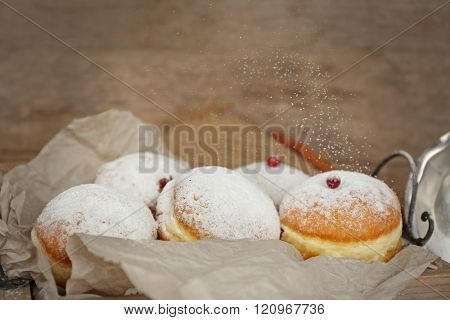 Delicious sugary donuts with red currant on wooden background