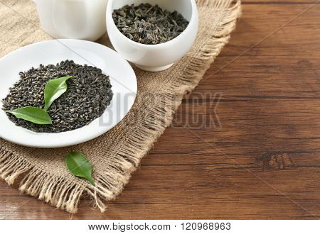 Dry tea with green leaves in plate and bowl on wooden table background