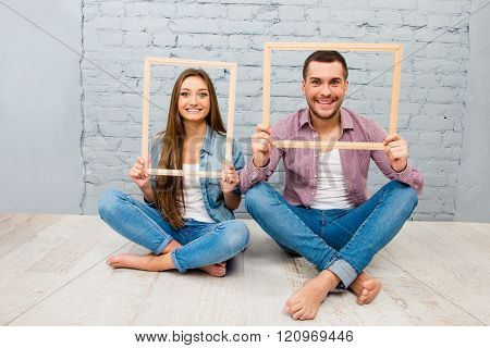 Happy Pretty Man And Woman Sitting Barefoot On The Floor With Wooden Frames