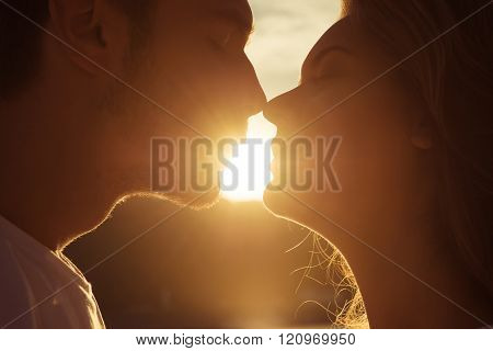Close Up Portrait Of Two Young Lovers Kissing On The Sunset