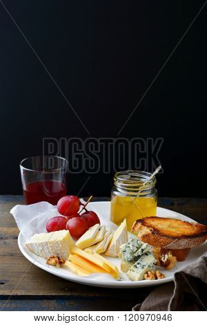 Cheese Plate With Grapes, Honey, Bread, Walnuts And Wine On Black Background